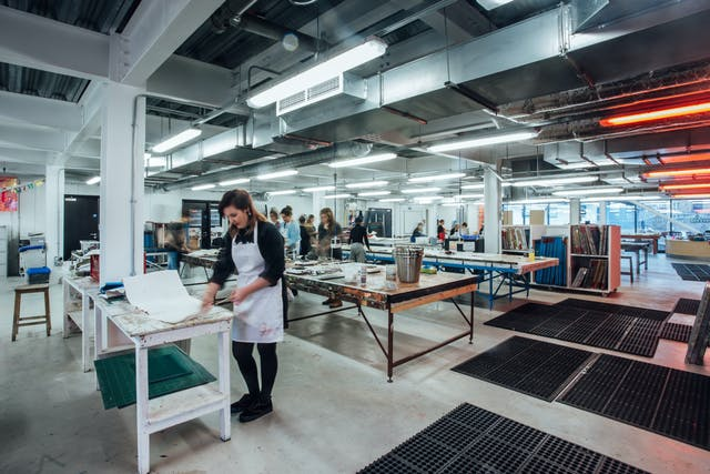 A wide angle shot of Plymouth College of Art's Fabric Lab consisting of work benches, resources and facilities for textiles, printmaking and dyeing