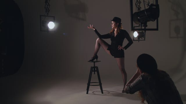 An image featuring a woman in the middle of the shot with her foot up on a stool, wearing a costume, she is surrounded by stage lights and in the foreground a photographer takes her image