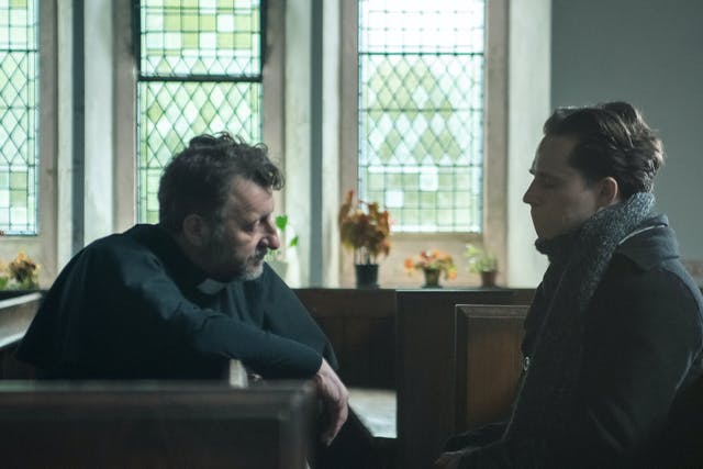 Picture features two characters in a church, on the left is a older man, a priest, speaking to a younger man on the right who's wearing a scarf and a heavy coat