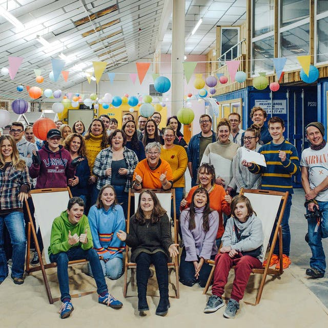A large group of people pose for a photograph in a large warehouse style room strung with colourful bunting and paper lanterns AYCH Creative Jam November 2019