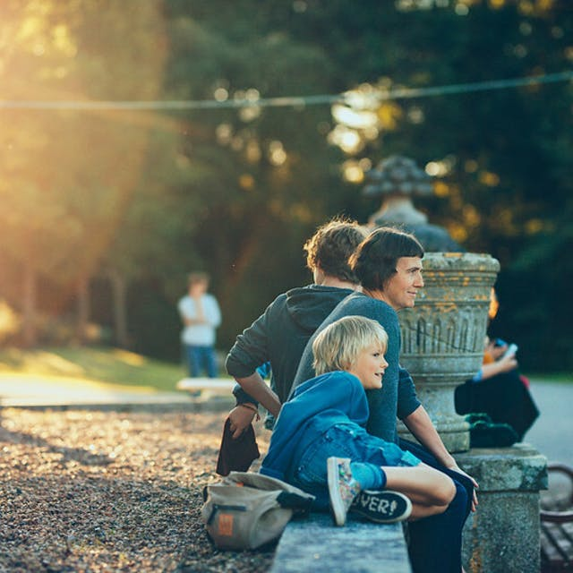 Making Futures 2017 an adult and child sit in the afternoon sun at Mount Edgcumbe Photo by Dom Moore