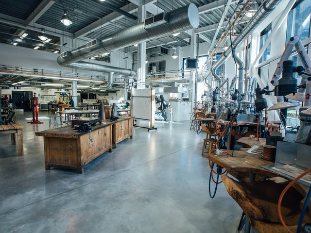 Our Jewellery Studio is a large, open space with high ceilings and full length windows to flood the workshop with natural light. Along the windows sits jewellery work stations with tools.