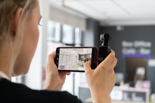 Female student records on an iphone, the device is held landscape in a grip to stabilise hand shakes. The camera screen is sharp and in focus, displaying the entrance way to the college's on-site cinema.